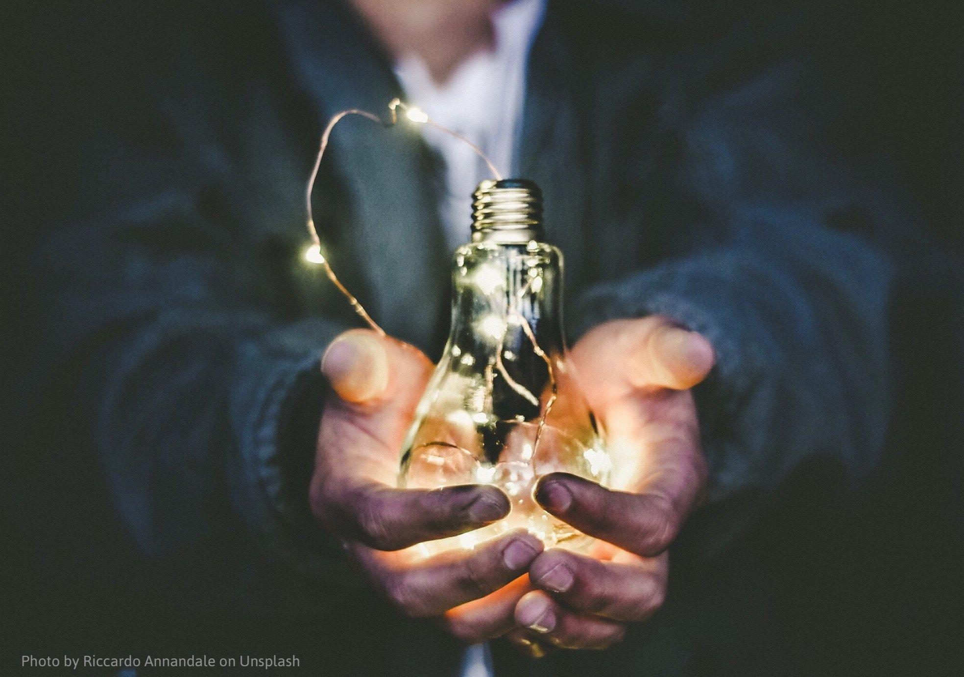 Hands holding light globe